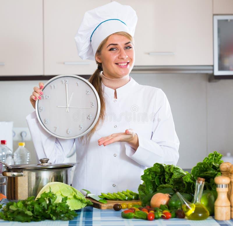 Fille dans l'uniforme de chef avec l'horloge et les veggies à la cuisine photo libre de droits