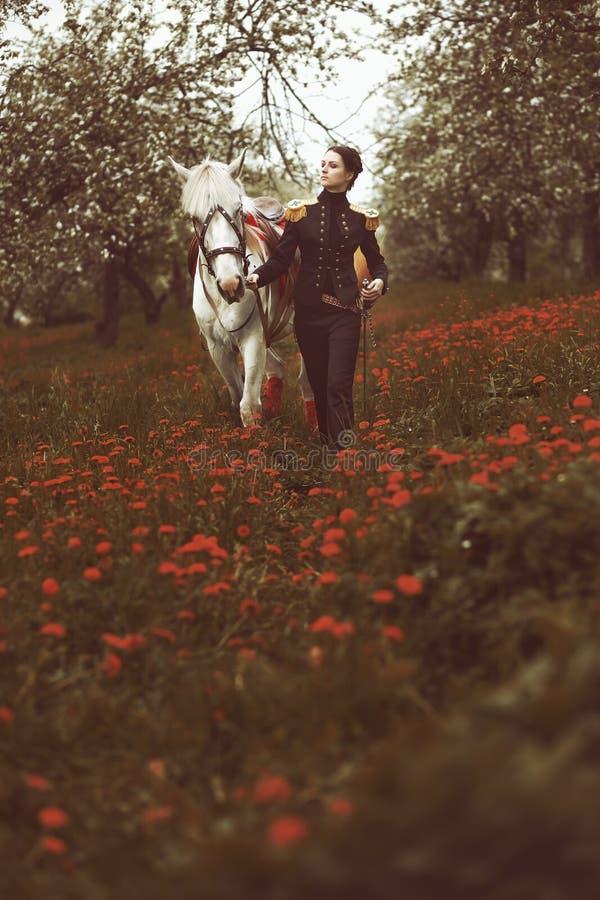Fille dans l'uniforme menant un cheval par le champ des fleurs photo libre de droits