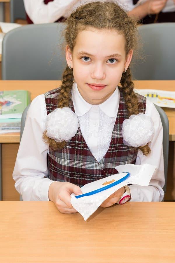 Fille dans l'uniforme scolaire faisant des devoirs sur le modèle sur le tissu photos stock