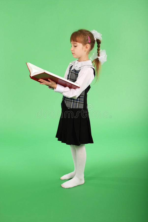 Fille dans l'uniforme scolaire lisant un livre photographie stock