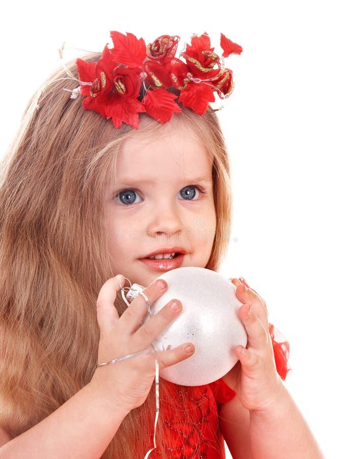 Fille dans la bille rouge de Noël de fixation de robe. image stock