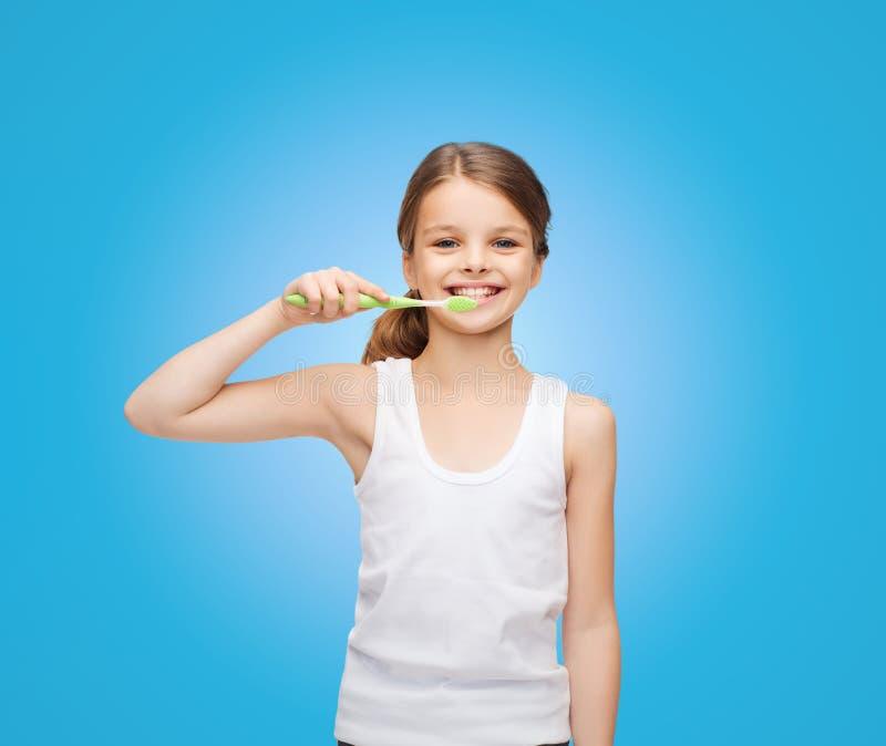 Fille dans la chemise blanche vide se brossant les dents images libres de droits