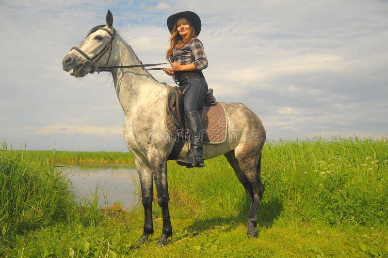 Fille dans la chemise de plaid et le chapeau de cowboy montant un cheval photo stock
