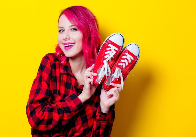 Fille dans la chemise et des chaussures en caoutchouc rouges de tartan photos libres de droits