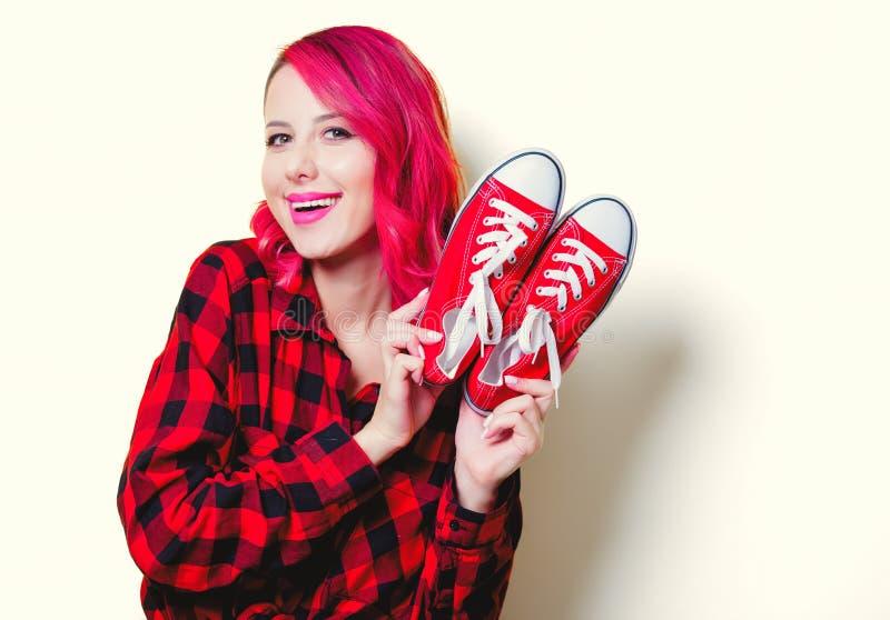 Fille dans la chemise et des chaussures en caoutchouc rouges de tartan image libre de droits
