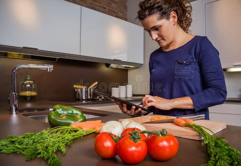 Fille dans la cuisine à la maison regardant la recette avec un comprimé électronique photos stock
