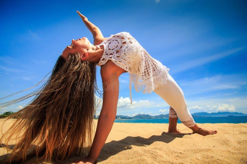 fille dans la dentelle dans l'équilibre de bras d'asana de yoga sur le plan rapproché de plage photographie stock
