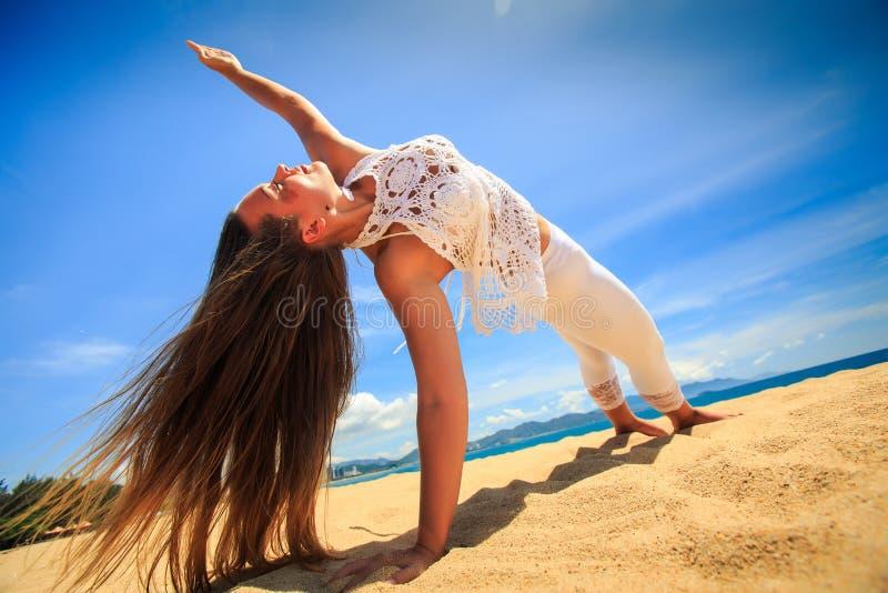 fille dans la dentelle dans l'équilibre de bras d'asana de yoga sur le plan rapproché de plage photographie stock libre de droits