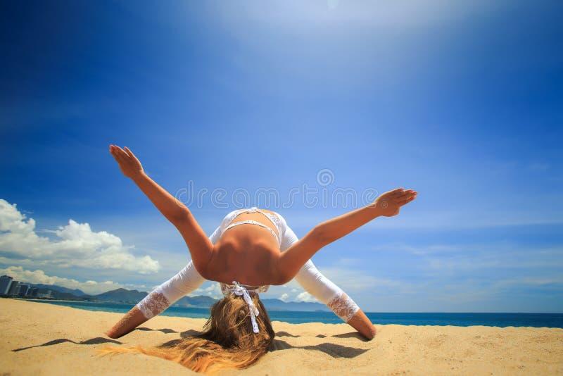 fille dans la dentelle dans l'équilibre principal orienté vers le bas d'asana de yoga sur la plage image stock