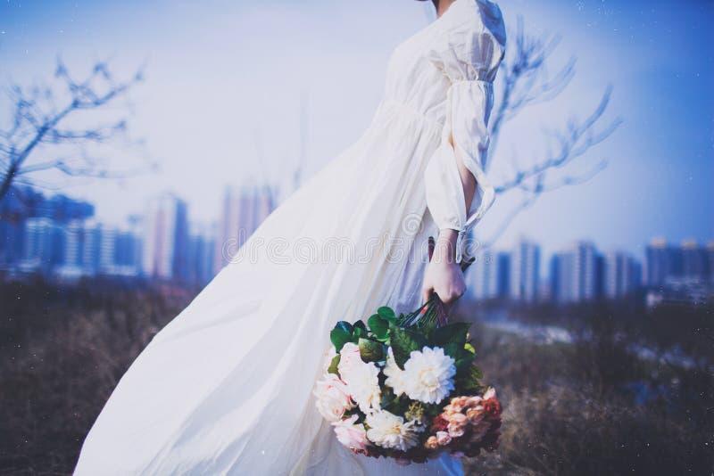 Fille dans la jupe blanche tenant des fleurs photos libres de droits