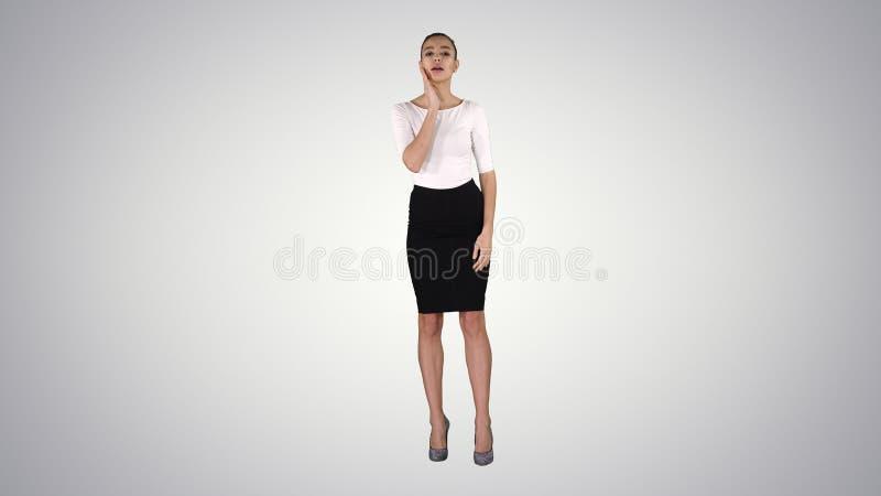 Fille dans la jupe lissant et vérifiant son aspect comme elle regarde dans le miroir sur le fond de gradient photos stock