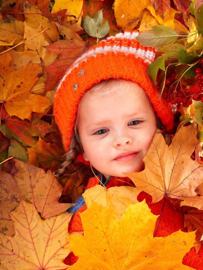 Fille dans la lame orange d'automne et la baie rouge. photos stock