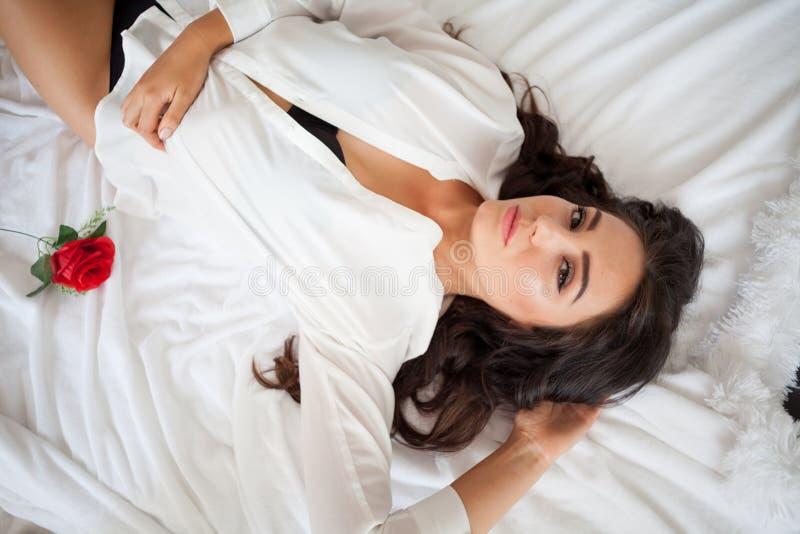 Fille dans la lingerie se trouvant sur un lit avec une rose image stock