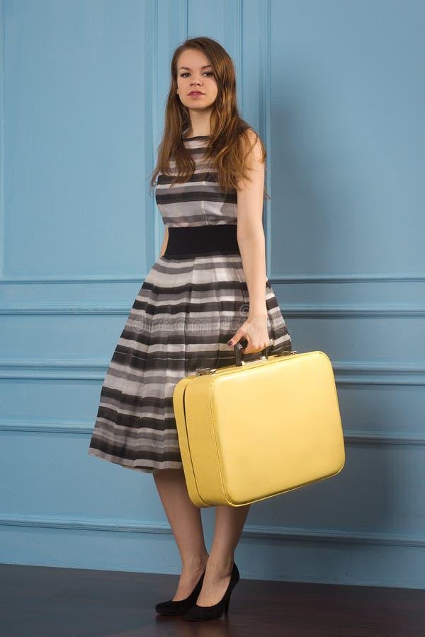 Fille dans la robe à pois démodée avec la vieille valise image libre de droits