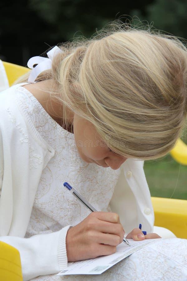Fille dans la robe blanche, écrivant image stock