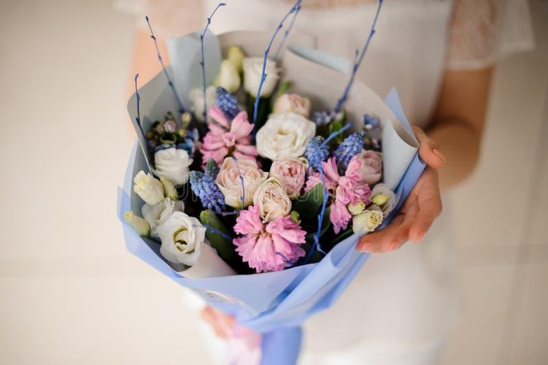 Fille dans la robe blanche tenant un bouquet de ressort de blanc tendre, de rose et de fleurs bleues photographie stock