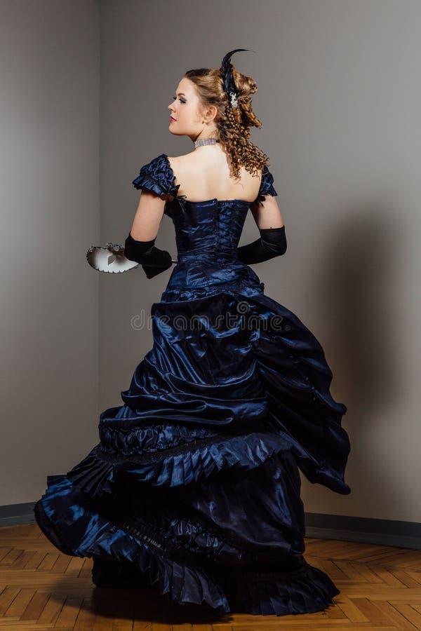 Fille dans la robe bleue de vintage avec le masque dans des mains Actrice dans le rôle Jeu du ` s d'acteur photos stock