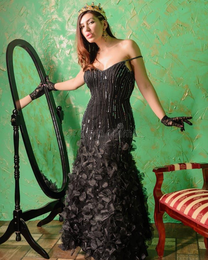 Fille dans la robe et la couronne de soirée noires sur sa tête photos libres de droits