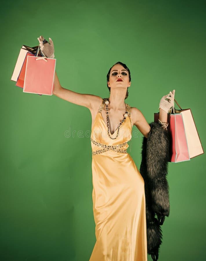 Fille dans la robe jaune, boa avec le sac ou paquet de cadeau photo libre de droits