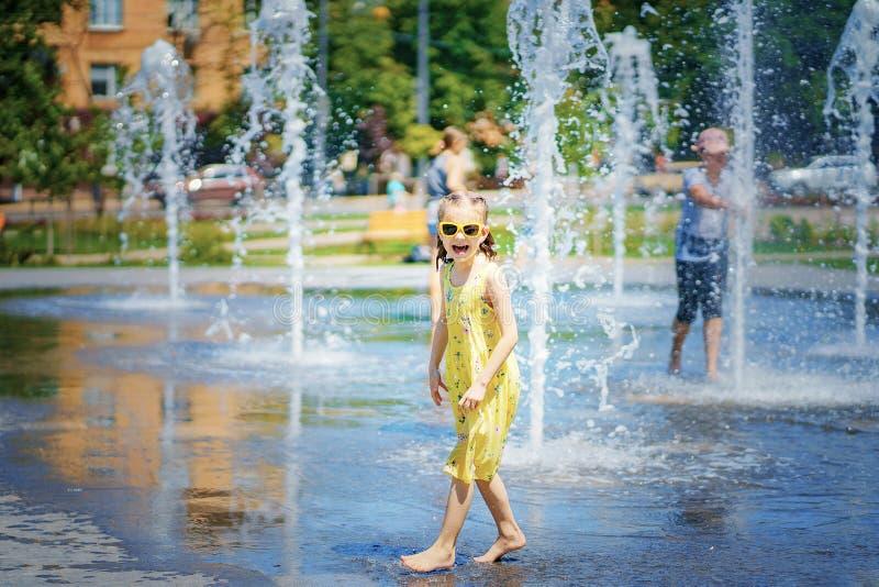 Fille dans la robe jaune jouant et ayant l'amusement appréciant le jet de la fontaine photos libres de droits
