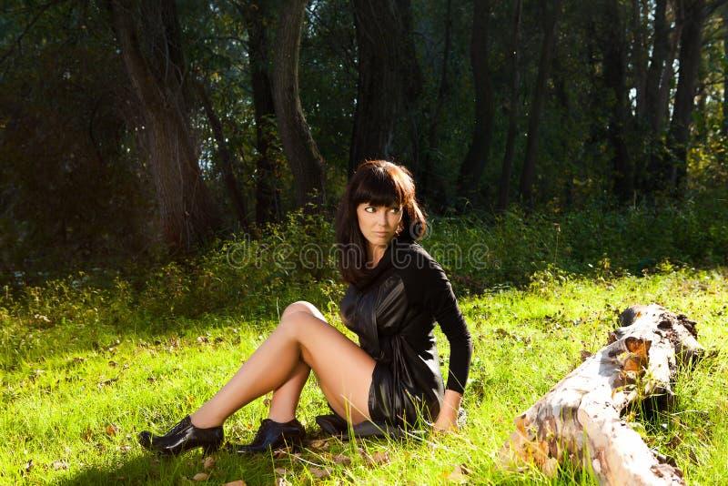 Fille dans la robe noire posant dans le dédouanement de la forêt de t photo stock