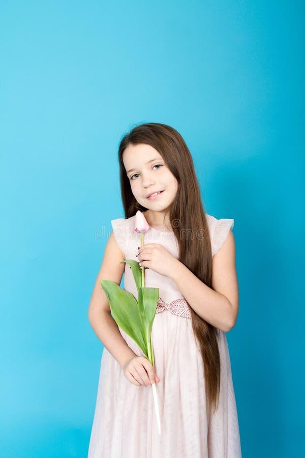 Fille dans la robe rose La fille prend la tulipe dans des ses mains images stock