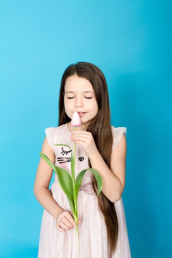 Fille dans la robe rose La fille prend la tulipe dans des ses mains photo stock
