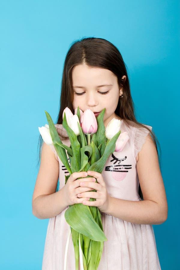 Fille dans la robe rose La fille prend la tulipe dans des ses mains image stock