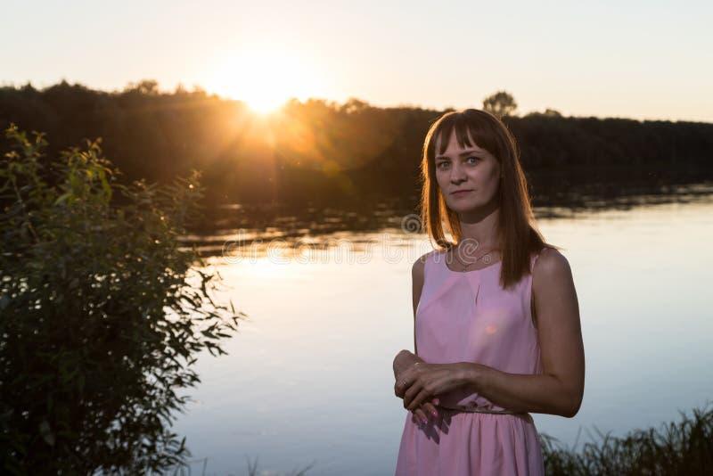 Fille dans la robe rose sur la plage de rivière pendant le coucher du soleil Fond extérieur de portrait et de soleil photos stock