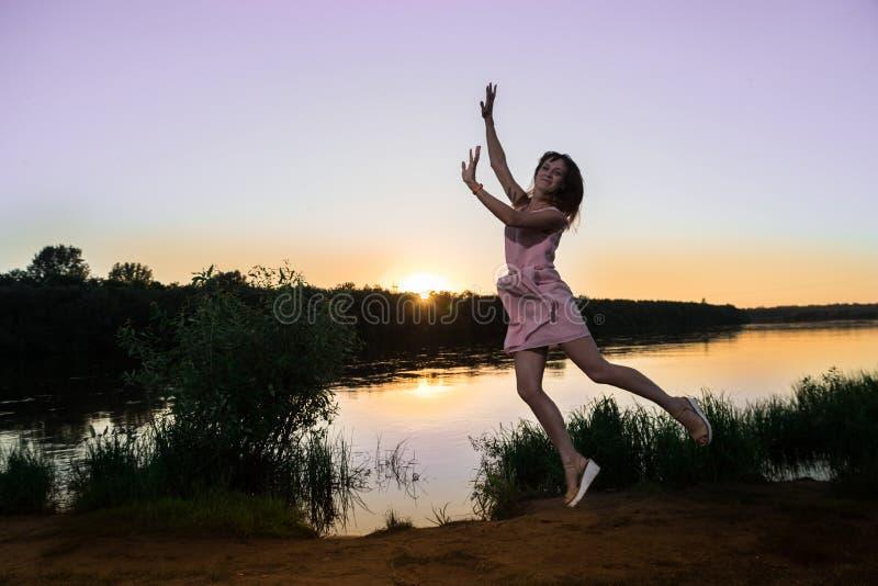 Fille dans la robe rose sur la plage de rivière pendant le coucher du soleil Fond extérieur de portrait et de soleil photographie stock libre de droits