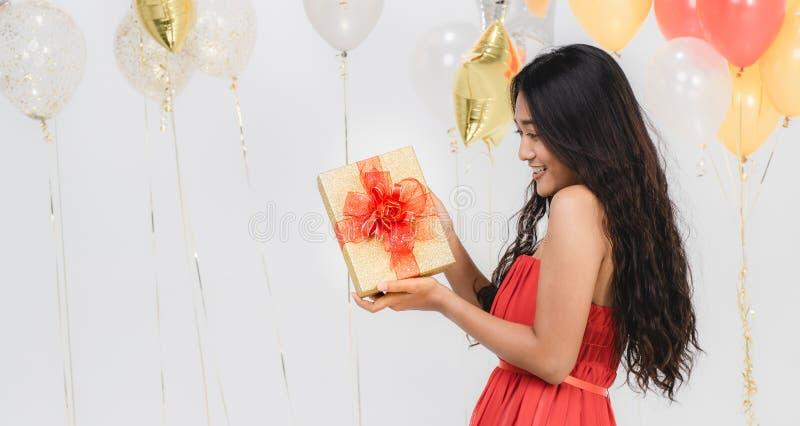 Fille dans la robe rouge avec le boîte-cadeau à la partie photographie stock libre de droits