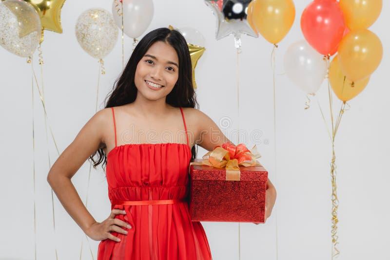 Fille dans la robe rouge avec le boîte-cadeau à la partie image stock