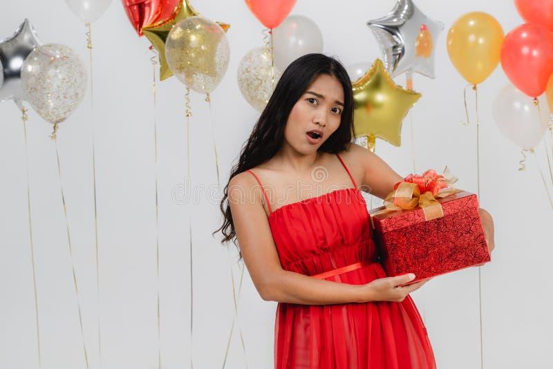 Fille dans la robe rouge avec le boîte-cadeau à la partie images stock