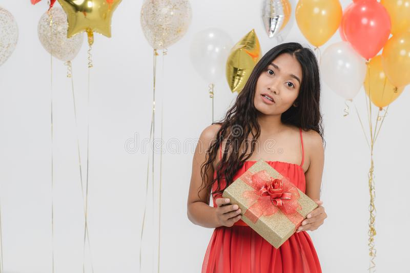 Fille dans la robe rouge avec le boîte-cadeau à la partie photo libre de droits