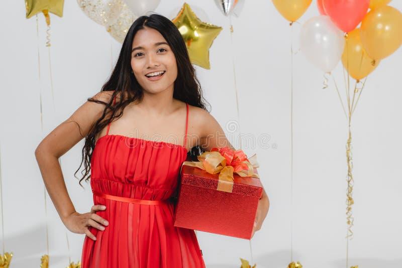 Fille dans la robe rouge avec le boîte-cadeau à la partie image libre de droits