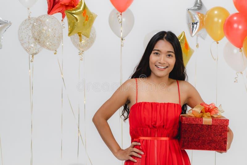 Fille dans la robe rouge avec le boîte-cadeau à la partie photo stock