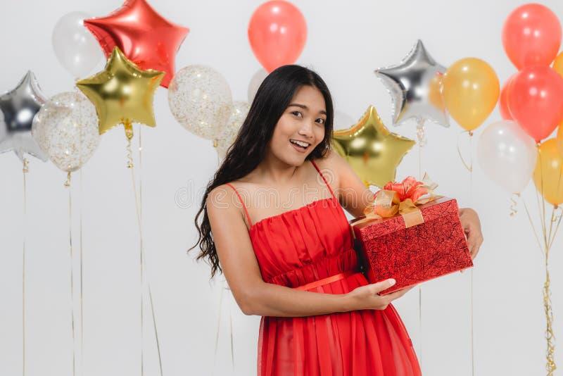 Fille dans la robe rouge avec le boîte-cadeau à la partie photographie stock