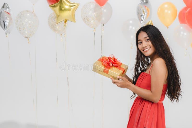 Fille dans la robe rouge avec le boîte-cadeau à la partie photos stock