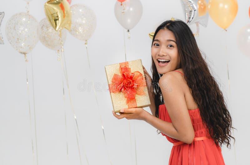 Fille dans la robe rouge avec le boîte-cadeau à la partie photos libres de droits