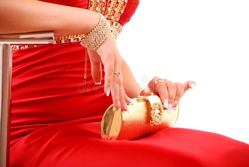 Fille dans la robe rouge avec le sac d'or photographie stock