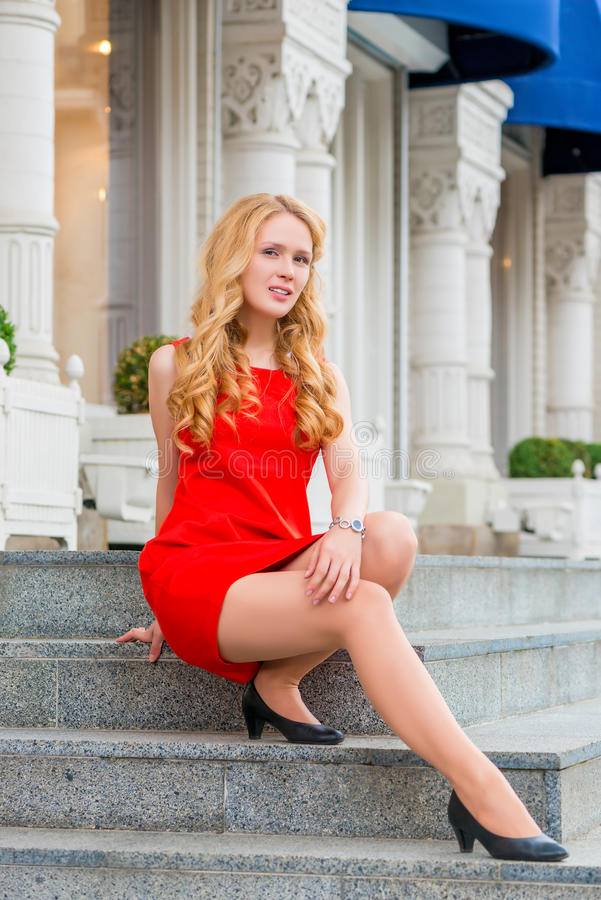 Fille dans la robe rouge se reposant sur les étapes image stock