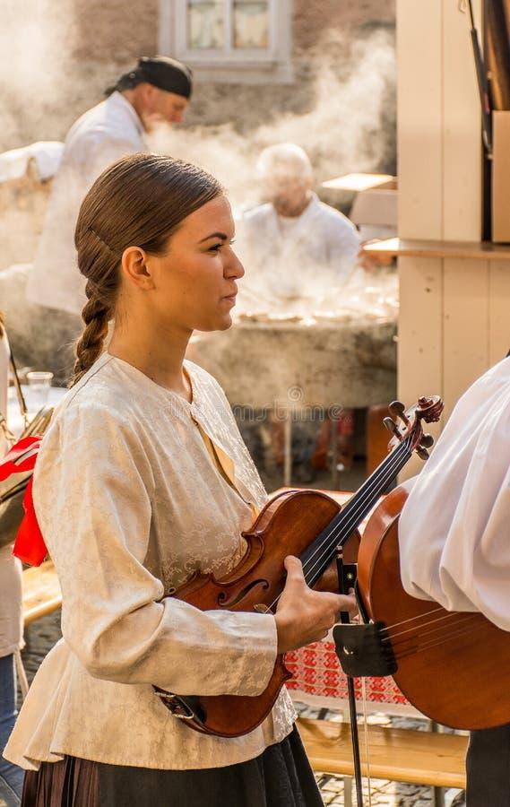 Fille dans la robe traditionnelle blanche et le violon de transport photographie stock libre de droits