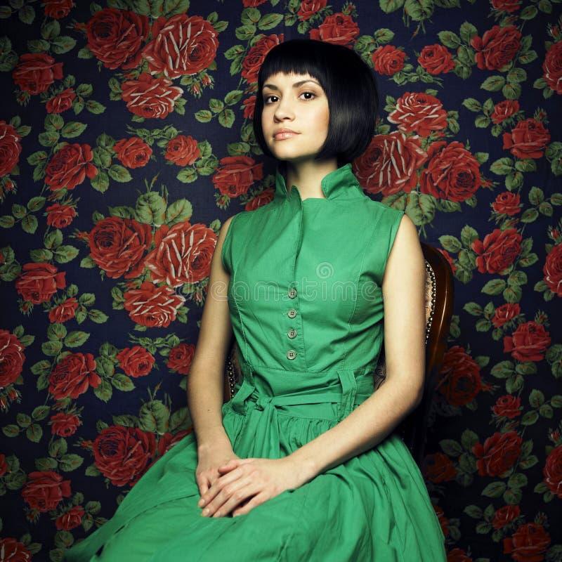 Fille dans la robe verte, entourée par des roses photographie stock