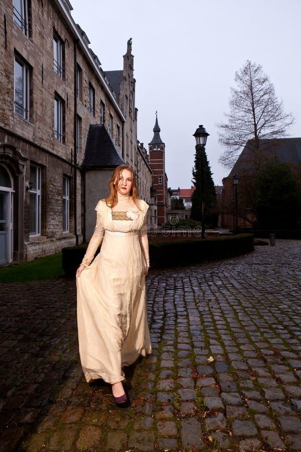 Fille dans la robe victorienne dans une vieille place de ville dans la marche de soirée photo stock