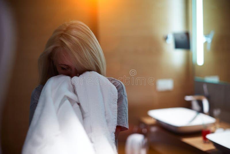 Fille dans la salle de bains appréciant l'odeur des serviettes blanches fraîches images stock