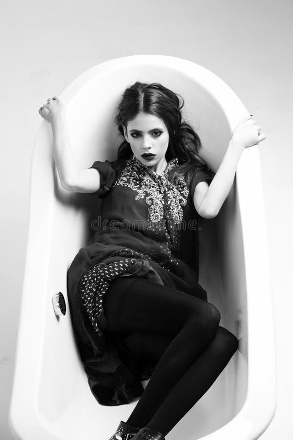 Fille dans la salle de bains femme dans la robe rouge avec les lèvres noires dans le bain images stock