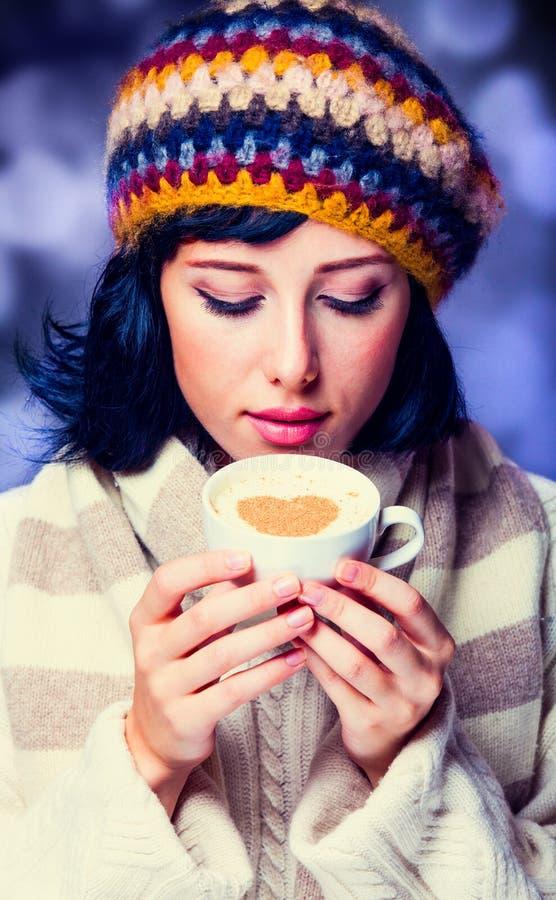 Fille dans la tasse de participation de béret et d'écharpe de café image stock