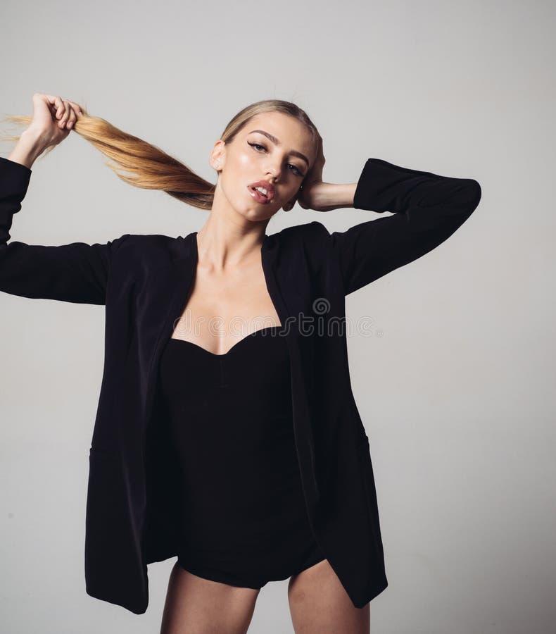 Fille dans la veste formelle et jeu decollete sexy avec ses longs beaux cheveux Madame sur le visage songeur posant dans le studi photographie stock