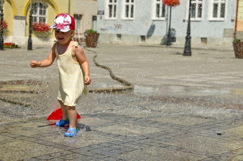 Fille dans la ville chaude d'été avec l'arroseuse de l'eau images libres de droits