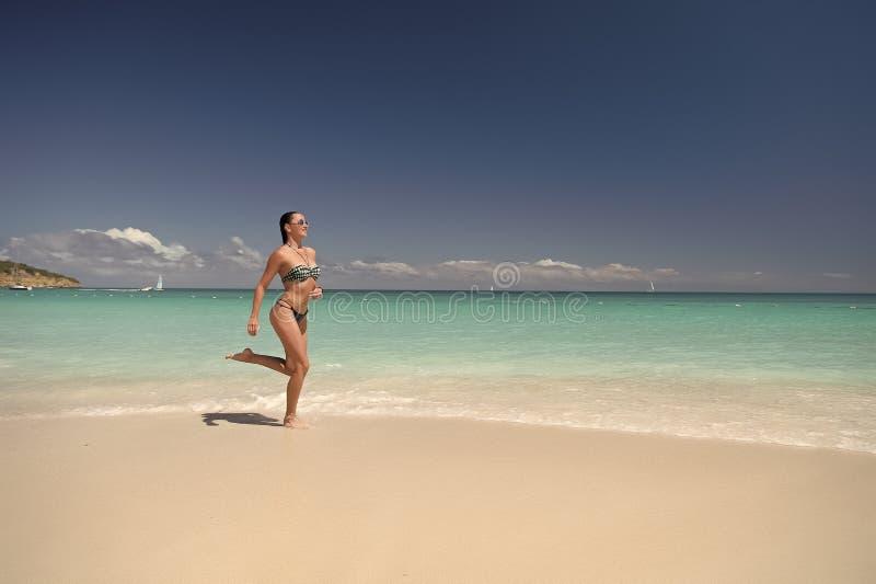 Fille dans le bikini fonctionnant sur la plage de mer photo libre de droits